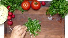 Τέμνοντες μαϊντανός και λαχανικά με ένα μαχαίρι σε έναν τέμνοντα πίνακα απόθεμα βίντεο