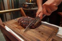 Τέμνον βόειο κρέας σχαρών στον ξύλινο τέμνοντα πίνακα στο εστιατόριο για Στοκ φωτογραφίες με δικαίωμα ελεύθερης χρήσης