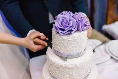 Τέμνον γαμήλιο κέικ με τα πορφυρά λουλούδια Στοκ φωτογραφία με δικαίωμα ελεύθερης χρήσης