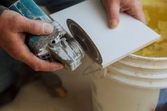 Τέμνον κεραμίδι εργαζομένων που χρησιμοποιεί το μύλο που κόβεται στα στρώματα των κεραμικών κεραμιδιών πατωμάτων στοκ εικόνα με δικαίωμα ελεύθερης χρήσης