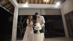 Τέμνον κομμάτι νυφών και νεόνυμφων του γαμήλιου κέικ στο κόμμα εορτασμού φιλμ μικρού μήκους