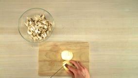 Τέμνον κρεμμύδι κουζινών στην ξύλινη τοπ άποψη πινάκων απόθεμα βίντεο