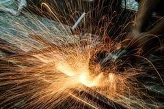 Τέμνον μέταλλο εργαζομένων με το μύλο αλέθοντας σπινθήρες σιδή Στοκ Εικόνες