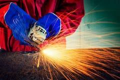 Τέμνον μέταλλο εργαζομένων με το μύλο Σπινθηρίζει ενώ Στοκ Φωτογραφίες