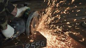 Τέμνον μέταλλο εργαζομένων συγκομιδών unrecognizable με το μύλο γωνίας στο εργοτάξιο οικοδομής απόθεμα βίντεο