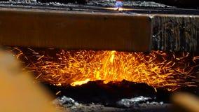 Τέμνον μέταλλο εργαζομένων με έναν φανό φλογών αερίου στη λειώνοντας βιομηχανία μετάλλων απόθεμα βίντεο