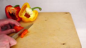 Τέμνον πορτοκαλί πιπέρι τσίλι με ένα μαχαίρι σε έναν ξύλινο πίνακα φιλμ μικρού μήκους