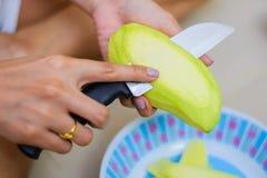 Τέμνον πράσινο δέρμα μάγκο από τα θηλυκά χέρια Στοκ Εικόνες