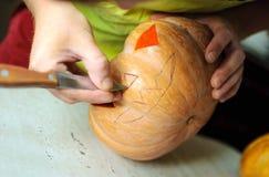 Τέμνουσα διαδικασία κολοκύθας αποκριών, διαδικασία το Jack-ο-φανάρι Αρσενικά χέρια με το μαχαίρι Στοκ φωτογραφία με δικαίωμα ελεύθερης χρήσης