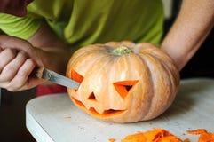 Τέμνουσα διαδικασία κολοκύθας αποκριών, διαδικασία το Jack-ο-φανάρι Αρσενικά χέρια με το μαχαίρι Στοκ Εικόνες
