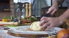 Τέμνουσα ζύμη μαγείρων αρχιμαγείρων με το μαχαίρι για το κέικ που ψήνει κοντά επάνω Τεμαχίζοντας ζύμη Baker για το κύλισμα στον ξ απόθεμα βίντεο