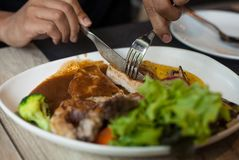 Τέμνουσα μπριζόλα μπριζολών χοιρινού κρέατος και δευτερεύον πιάτο Στοκ Φωτογραφία
