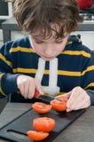τέμνουσα ντομάτα αγοριών στοκ εικόνα με δικαίωμα ελεύθερης χρήσης
