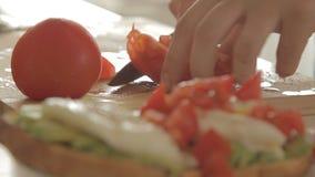 Τέμνουσα ντομάτα γυναικών για το υγιές πρόγευμα με το αβοκάντο στο ψημένες ψωμί, τα αυγά και την ντομάτα απόθεμα βίντεο