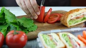 Τέμνουσα ντομάτα γυναικών στον ξύλινο πίνακα, σάντουιτς στο καλαθάκι με φαγητό στο υπόβαθρο Σάντουιτς προετοιμασιών για την εργασ φιλμ μικρού μήκους
