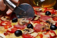 Τέμνουσα φρέσκια πίτσα Στοκ Φωτογραφία