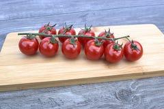 τέμνουσες ντομάτες κερασιών χαρτονιών Στοκ Εικόνες