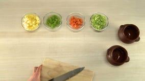 Τέμνουσες πατάτες κουζινών στην ξύλινη τοπ άποψη πινάκων απόθεμα βίντεο