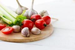Τέμνων πίνακας με τα φρέσκα λαχανικά στον άσπρο ξύλινο πίνακα Copyspace Στοκ Φωτογραφίες