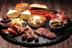 Τέμνων πίνακας με το prosciutto, το σαλάμι, το τυρί, το ψωμί και τις ελιές στο σκοτεινό υπόβαθρο πετρών στοκ εικόνες