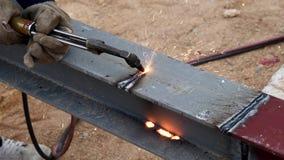 Τέμνων σίδηρος με το φανό αερίου στην εργασία στο εργοτάξιο οικοδομής απόθεμα βίντεο