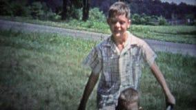 ΤΈΝΕΣΙ, ΗΠΑ - 1953: Παλαιότερος αδελφός που ωθεί γύρω από το παιδί wheelbarrow για τη θερινή διασκέδαση απόθεμα βίντεο