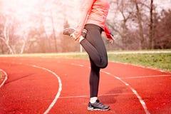 Τέντωμα γυναικών σε μια τρέχοντας διαδρομή Στοκ εικόνες με δικαίωμα ελεύθερης χρήσης