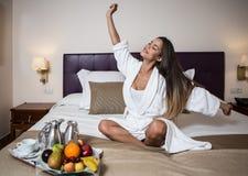 Τέντωμα γυναικών στο κρεβάτι του δωματίου ξενοδοχείου στοκ εικόνα με δικαίωμα ελεύθερης χρήσης