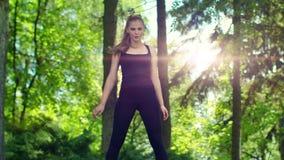 Τέντωμα γυναικών στο πάρκο στο πρωί άσκηση της υπαίθριας γυναίκας φιλμ μικρού μήκους