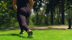 Τέντωμα γυναικών υπαίθριο Κορίτσι ικανότητας που κάνει lunges στο πάρκο Workout και ικανότητα φιλμ μικρού μήκους