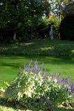 Τέντωμα Cepuglio του ποταμού με τα μπλε λουλούδια που οριοθετούν το χορτοτάπητα που βρίσκεται απέναντι από το κάστρο Strassoldo F Στοκ Εικόνα