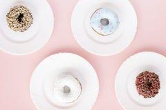 Τέσσερα άσπρα πιάτα με τα διαφορετικά donuts που καλύπτονται με το λούστρο Στοκ φωτογραφία με δικαίωμα ελεύθερης χρήσης
