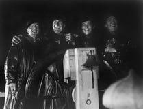 Τέσσερα άτομα στα slickers που στέκονται μαζί στη ρόδα του καπετάνιου ενός σκάφους (όλα τα πρόσωπα που απεικονίζονται δεν ζουν πε Στοκ Εικόνες