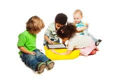 Τέσσερα παιδιά που παίζουν τον υπολογιστή ταμπλετών Στοκ εικόνες με δικαίωμα ελεύθερης χρήσης