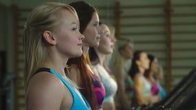 Τέσσερα αθλητικά κορίτσια πηγαίνουν συγχρόνως treadmills, σε αργή κίνηση απόθεμα βίντεο