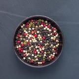 Τέσσερα διαφορετικά είδη peppercorns στον άργιλο κυλούν στο υπόβαθρο πετρών, τοπ άποψη, τετράγωνο Στοκ εικόνα με δικαίωμα ελεύθερης χρήσης