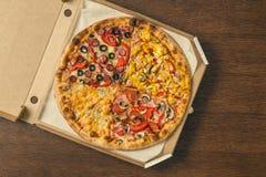 Τέσσερα διαφορετικά κομμάτια της πίτσας στο ανοικτό κιβώτιο παράδοσης Στοκ Εικόνες