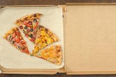 Τέσσερα διαφορετικά κομμάτια της πίτσας στο ανοικτό κιβώτιο παράδοσης Διάστημα για το κείμενο Στοκ εικόνα με δικαίωμα ελεύθερης χρήσης