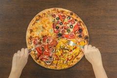 Τέσσερα διαφορετικά μέρη της πίτσας με το μαχαίρι στον ξύλινο πίνακα Στοκ Εικόνα