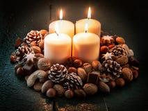Τέσσερα ευρέα κεριά που περιβάλλονται από τα καρύδια και τους κώνους Στοκ εικόνα με δικαίωμα ελεύθερης χρήσης