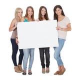 Τέσσερα ελκυστικά κορίτσια που κρατούν ένα λευκό χαρτόνι Στοκ φωτογραφία με δικαίωμα ελεύθερης χρήσης