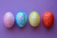 Τέσσερα ζωηρόχρωμα αυγά Πάσχας στο πορφυρό υπόβαθρο Στοκ φωτογραφία με δικαίωμα ελεύθερης χρήσης