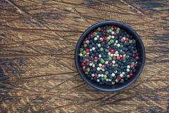 Τέσσερα διαφορετικά είδη peppercorns στο κύπελλο αργίλου στο ξύλινο υπόβαθρο, αντιγράφουν τη διαστημική, τοπ άποψη Στοκ φωτογραφίες με δικαίωμα ελεύθερης χρήσης