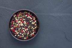 Τέσσερα διαφορετικά είδη peppercorns στο κύπελλο αργίλου στο υπόβαθρο πετρών, αντιγράφουν τη διαστημική, τοπ άποψη Στοκ Φωτογραφίες
