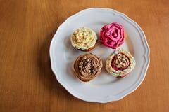 Τέσσερα διαφορετικά σπιτικά cupcakes στο πιάτο πέρα από το ξύλινο υπόβαθρο Στοκ εικόνα με δικαίωμα ελεύθερης χρήσης