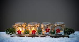 Τέσσερα κεριά εμφάνισης στο χιόνι Στοκ Εικόνες