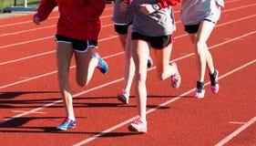 Τέσσερα κορίτσια που εκπαιδεύουν μαζί σε μια κόκκινη διαδρομή στις ακίδες Στοκ Φωτογραφίες