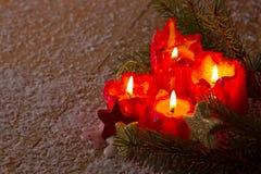 Τέσσερα κόκκινα κεριά εμφάνισης με τη διακόσμηση Χριστουγέννων Στοκ Εικόνες