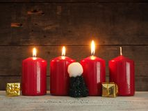 Τέσσερα κόκκινα κεριά εμφάνισης στο ξύλο Στοκ Φωτογραφίες
