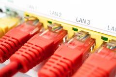 Τέσσερα κόκκινα σκοινιά μπαλωμάτων παρεμβάλλονται σε έναν άσπρο δρομολογητή ανασκόπησης μπλε καλωδίων βύσμα Διαδικτύου σύνδεσης β Στοκ Εικόνες